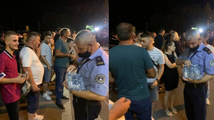 Police distribute water to the families of the survivors who